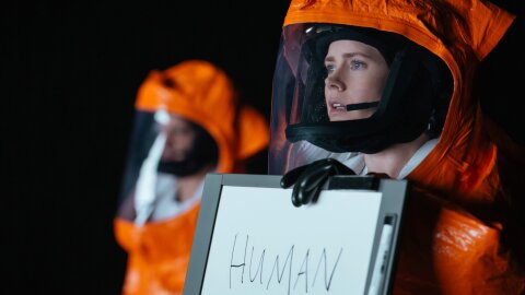 Human in a hazmat suit with a whiteboard Arrival movie backdrop