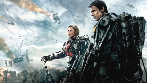 Tom Cruise and Emily Blunt standing badass in power armor before a scene of destruction