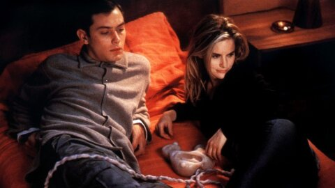 Sexy people on a bed but with yucky Cronenberg stuff, thus ruining it. eXistenZ movie backdrop.