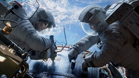 Astronauts working on Hubble with no danger in sight, Gravity backdrop