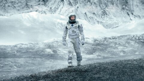Interstellar Matthew McConaughey in a spacesuit on an icy planet movie backdrop