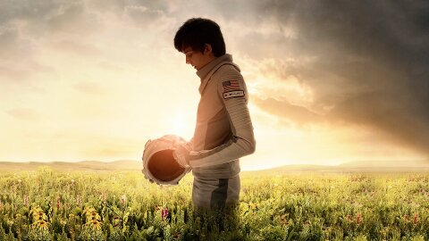 Asa Butterfield standing in a spacesuit in a field on Earth, Space Between Us movie backdrop
