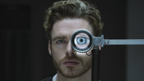 Rob Stark, but in the future, doing an eye test. Oasis tv pilot backdrop.